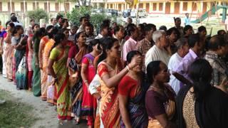 पश्चिम बंगाल के कूच बिहार के एक मतदान केंद्र पर पहुंचे मतदाता