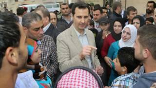 الرئيس السوري بشار الأسد يتحدث مع مواطنين سوريين أثناء زيارة مفاجئة لإحدى المناطق