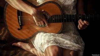 Mulher tocando violão   Foto: Thinkstock