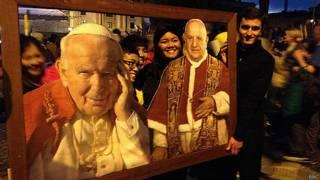 Fieis posam com quadro de João Paulo 2º e João 23 no Vaticano | Foto: BBC