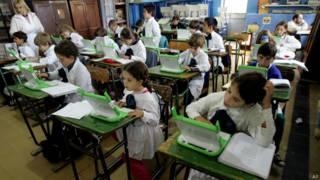 Crianças estudam com laptops no Uruguai, em foto de arquivo (AP)