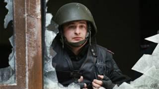 Policía ucraniano mira por la ventana rota de la oficina del fiscal regional