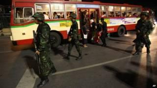 أفراد من الجيش التايلاندي يحرسون الشوارع، ومواطنين يستقلون حافلة