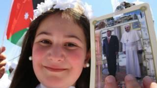 Menina segura foto do papa com o rei Abdullah da Jordânia (AP Photo/Raad Adayleh)