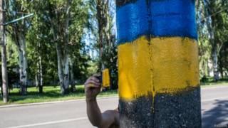 рука рисует украинский флаг на дереве