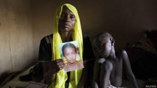 Mulher segura foto de filha sequestrada (Reuters)