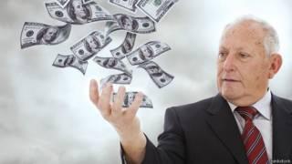 Пожилой мужчина швыряет деньги в воздух