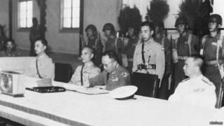 1945年9月9日,中国战区日军投降签字仪式在南京举行,图为中方受降代表何应钦(前右二)在日军降书上签字。