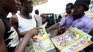 लागोस में फ़ुटबॉल विश्व कप का कार्यक्रम बेचता एक व्यक्ति