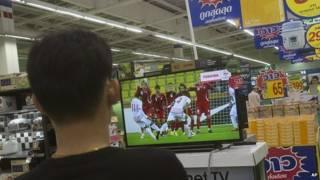 Tailandés viendo fútbol por televisión