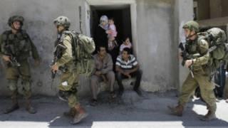 Wapalestina wakaa nje ya nyumba yao huku askari wa Israel wanapiga doria mjini Hebron, Ufukwe wa Magharibi