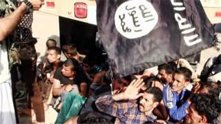 флаг джихадистов и захваченные ими люди
