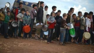 لاجئون سوريون ينتظرون الحصول على الغذاء