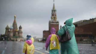 Холодный июнь 2014 года - туристы в плащах и куртках идут по Красной площади в Москве