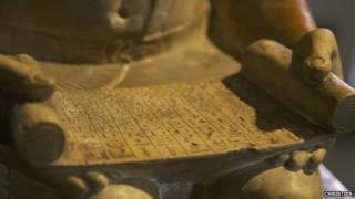 مخطوطة في يد التمثال