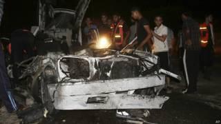 Palestinos con auto destruido en Rafah, Gaza