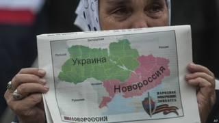 Женщина держит карту Украины, разделенную на две части