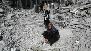 Una mujer en medio de los escombros en Beit Hanun