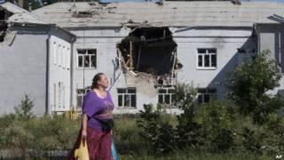 Женщина на фоне разрушенного дома на Украине (26 июля )