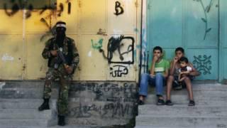 Niños en la Franja de Gaza con un militante armado