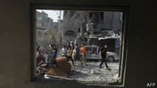 Wapalestina waangalia mabaki ya jengo liloshambuliwa Jumamosi na Israil, kusini mwa Gaza, huko Rafah