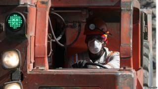 Рабочий управляет машиной вывозящей руду
