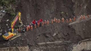 عمال الإنقاذ يسيرون على حافة أحد التلال