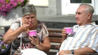 Пенсионеры едят мороженое на Кузнецком Мосту в Москве 3 августа 2014 года