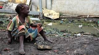 Niña jugando entre barro y basura en Malakal, Sudán del Sur