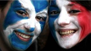 Pareja con las banderas de Escocia y Francia pintadas