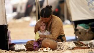 Mujer y niña sirias refugiadas.