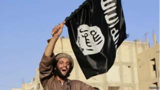 أحد أنصار الدولة الإسلامية يرفع علم التنظيم