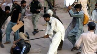 محتج يضرب رجل شرطة بعصاة