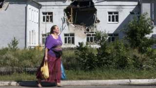 Местная жительница на фоне поврежденной школы в городе Лисичанск, Луганская область