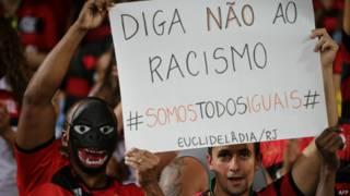 Torcedores exibem cartaz criticando o racismo no futebol