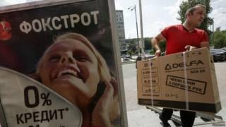 Hombre con caja de producto electrónico en Kiev (foto de archivo)