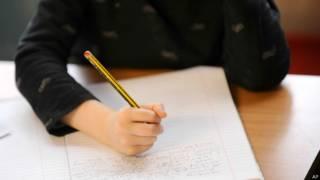 Criança escrevendo na escola / Crédito: AP