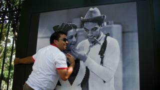 Un hombre posa ante la foto de Cantinflas en el centenario de su nacimiento. Foto: AFP/Getty
