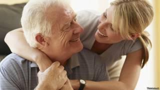 Отец и взрослая дочь улыбаются друг другу