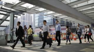 Люди идут на работу в правительственном квартале Гонконга