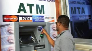 Homem usa caixa eletrônico inaugurado na Somália / Crédito: AFP