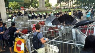 香港「佔領中環」行動參與者在幹諾道中中環段隔著剩餘路障與警察對峙  (BBC中文網圖片13/10/2014)