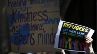 متظاهر يرفع لافتة لدعم حقوق اللاجئين
