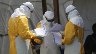ممرضون يرتدون الملابس الواقية من إيبولا وينظرون في أوراق