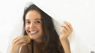 Una mujer debajo de las sábanas comiendo galletas