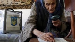 سيدة مسنة تقرأ ورقة التصويت بعدسة مكبرة