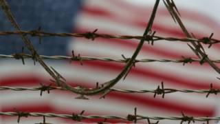 Флаг США на фоне тюремной решетки