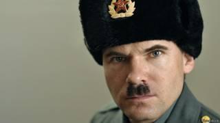 Злобно глядящий мужчина в советской военной шапке