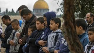 رجال يصلون وفي الخلفية مسجد قبة الصخرة