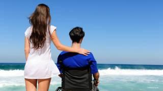 Mujer junto a un hombre en silla de ruedas